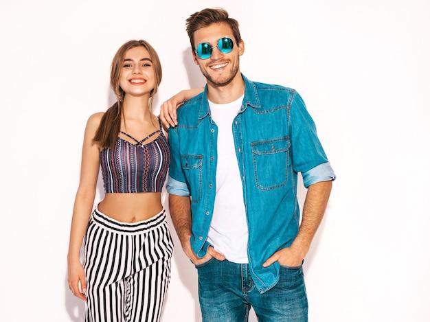Retrato de menina bonita sorridente e seu namorado considerável rindo. feliz casal alegre em óculos de sol redondos. dia dos namorados. abraçando Foto gratuita
