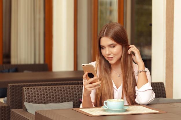 Retrato de menina bonita, usando seu telefone celular no café Foto Premium