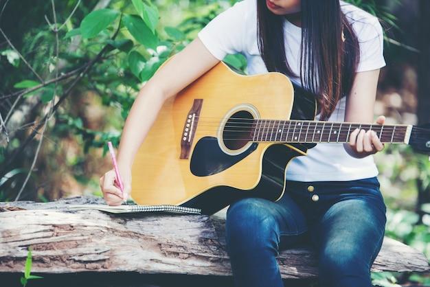 Retrato, de, menina bonita, violão jogo, com, escrita, em, natureza Foto gratuita