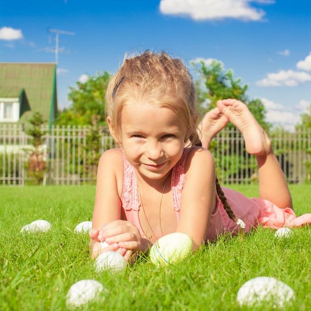 Retrato de menina bonitinha brincando com ovos de páscoa brancos na grama verde Foto Premium