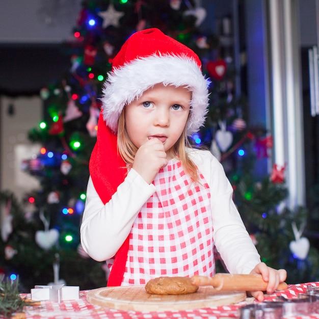 Retrato de menina com rolo de massa assar biscoitos de gengibre para o natal Foto Premium