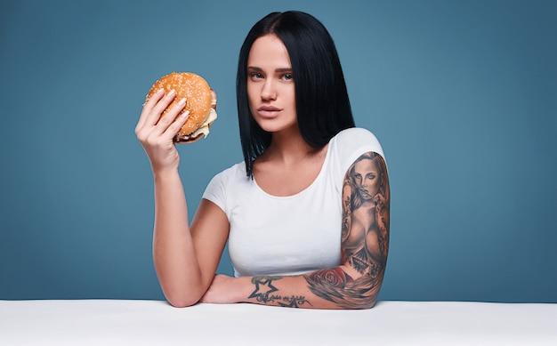 Retrato de menina encantadora tatuagem bonita segurando o hambúrguer Foto Premium