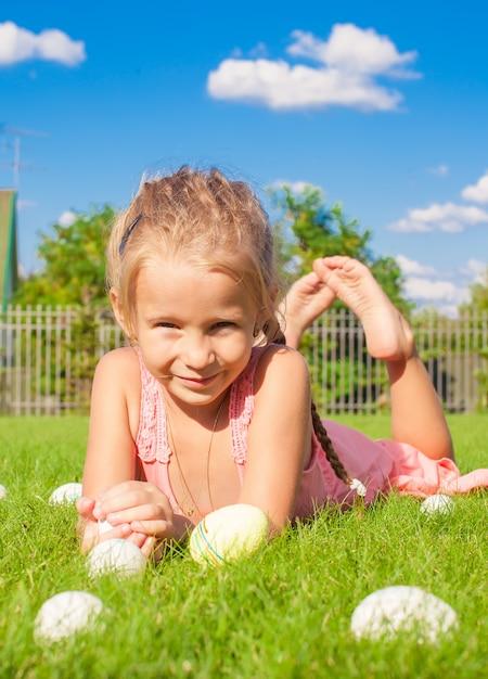 Retrato de menina feliz brincando com ovos de páscoa brancos na grama verde Foto Premium