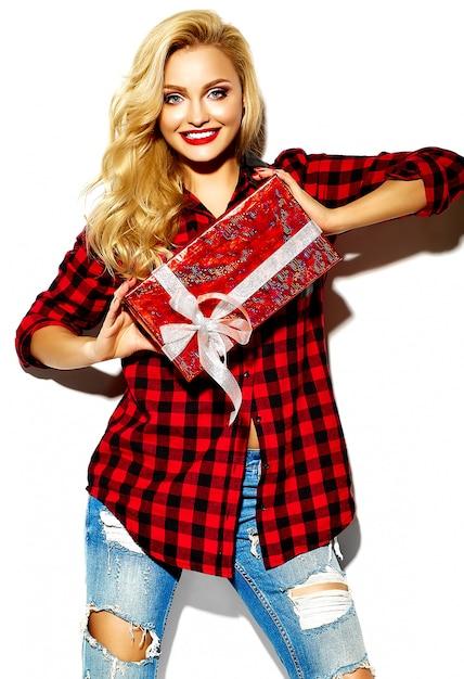 Retrato de menina feliz doce sorridente mulher loira bonita segurando nas mãos caixa de presente de natal em roupas de camisa de flanela xadrez inverno casual vermelho hipster e jeans azul Foto gratuita