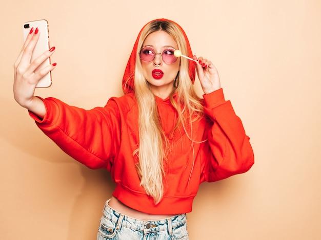 Retrato de menina má hipster jovem bonita em roupas da moda jeans e brinco no nariz. mulher loira sorridente despreocupada sexy leva selfie. modelo positivo lambendo doces de açúcar redondos Foto gratuita