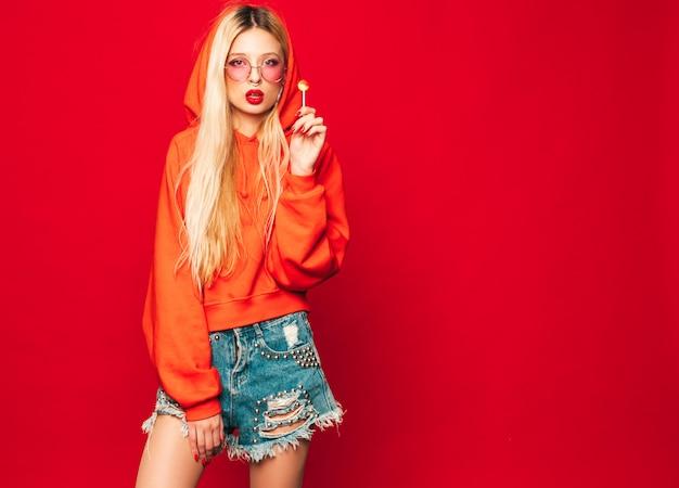 Retrato de menina má jovem hippie bonito no capuz vermelho na moda e brinco no nariz. modelo positivo lambendo doces de açúcar redondos Foto gratuita