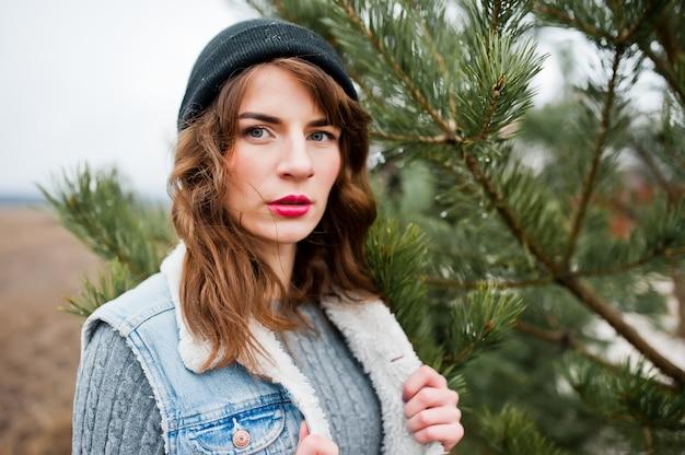 Retrato de menina morena no chapéu e jaqueta jeans na árvore. Foto Premium