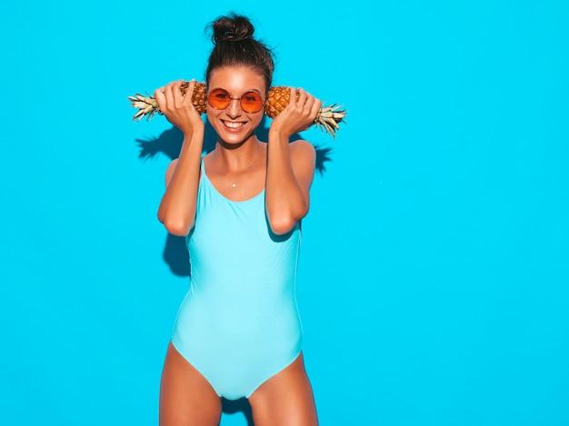 Retrato de menina morena sorridente em maiô de moda praia e óculos de sol. mulher sexy com abacaxis pequenos frescos. positivo modelo posando perto da parede azul. segure perto das orelhas Foto gratuita