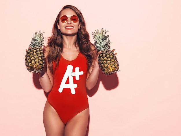 Retrato de menina morena sorridente em roupas de banho vermelho verão e óculos de sol redondos. mulher sexy com abacaxis frescos. posando modelo positivo Foto gratuita