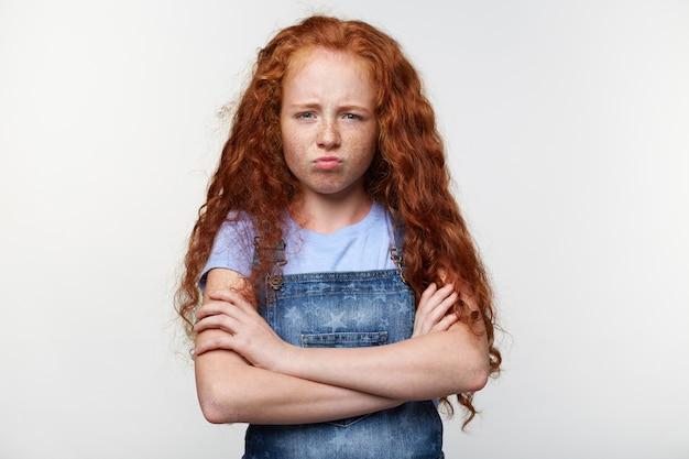 Retrato de menina sardenta infeliz com cabelos ruivos, em pé sobre uma parede branca com os braços cruzados, parece triste e ofendida. Foto gratuita