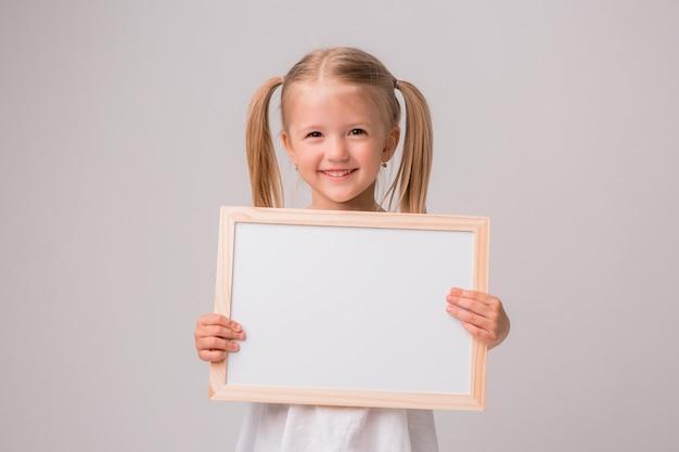 Retrato de menina segurando o quadro de desenho branco sobre fundo branco Foto Premium