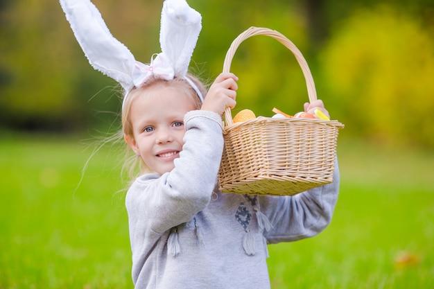 Retrato, de, menininha, com, um, cesta, cheio, ovos páscoa, ligado, primavera, dia, ao ar livre Foto Premium