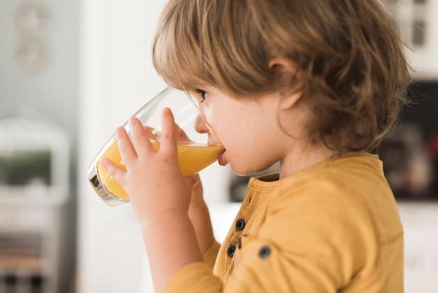 Retrato de menino bebendo copo de suco de laranja Foto gratuita