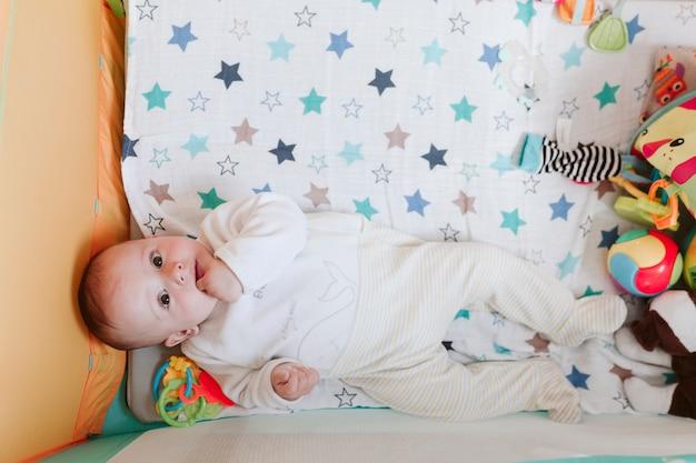 Retrato de menino bonito em um berço, olhando curioso para a câmera Foto Premium