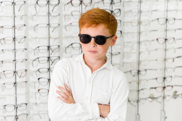 Retrato de menino com óculos pretos de pé contra o fundo de óculos Foto gratuita