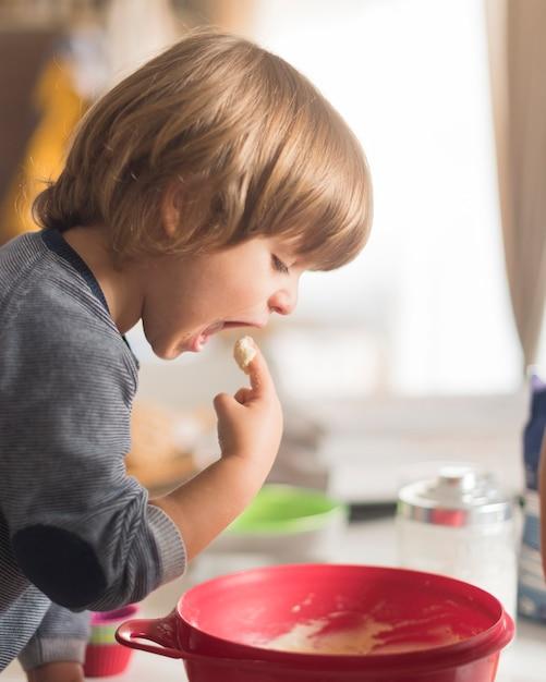 Retrato de menino degustação massa Foto gratuita