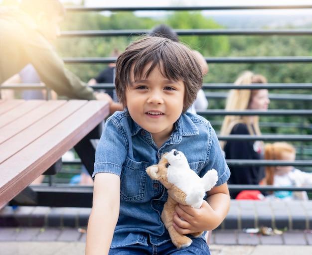 Retrato de menino feliz, abraçando a localização de brinquedo de cachorro no banco de madeira e fazendo careta Foto Premium