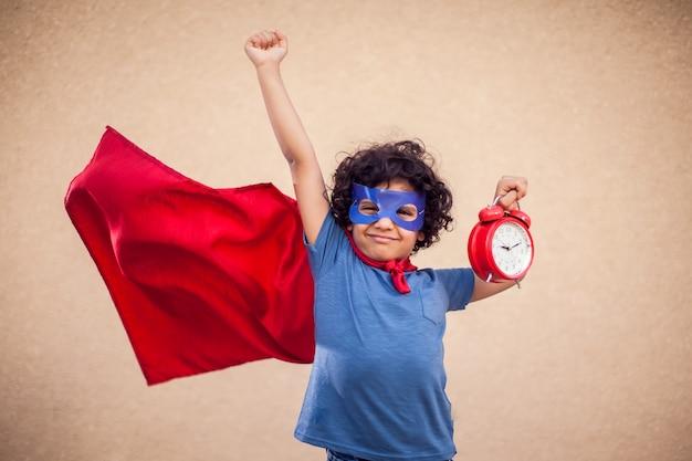 Retrato de menino garoto com cabelos cacheados em traje de super-herói segurando o relógio despertador. conceito de gestão de infância, sucesso e tempo Foto Premium