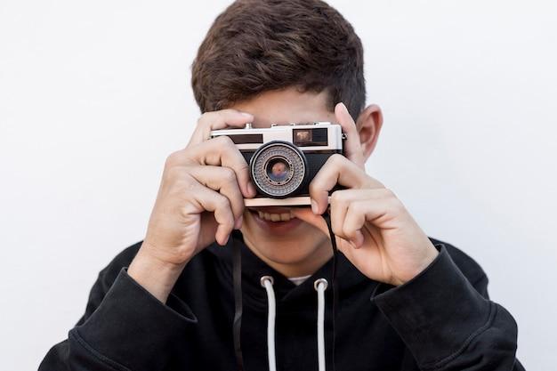 Retrato, de, menino jovem, fazendo exame retrato, através, retro, câmera, branco, fundo Foto gratuita