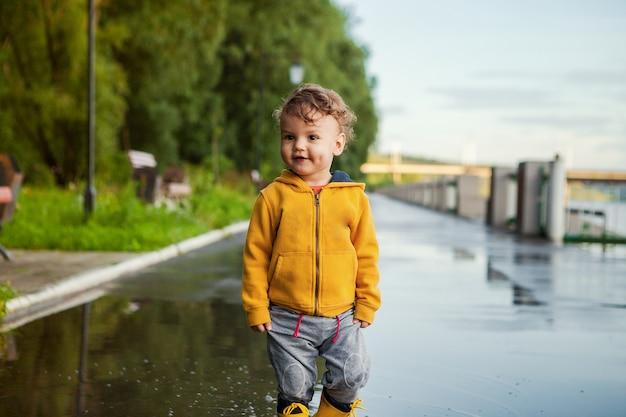 Retrato de menino lindo garoto sorridente. criança feliz contra árvore verde. garoto brincando ao ar livre. rindo menino saudável no casaco de chuva amarelo Foto Premium