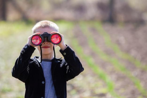 Retrato de menino loiro bonitinho bonito bonitinho assistindo atentamente algo através de binóculos na distância Foto Premium