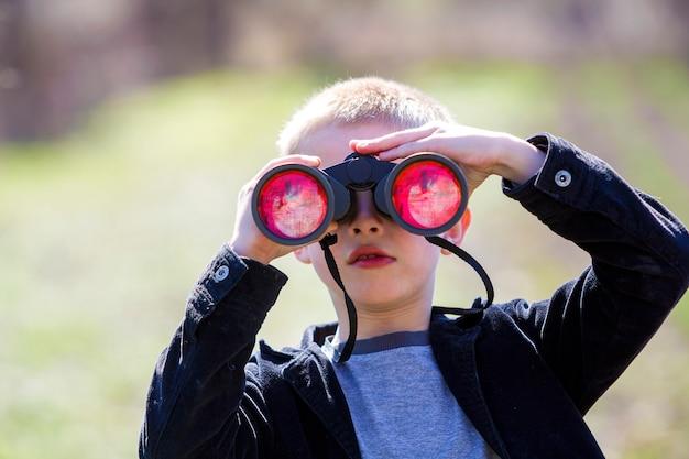 Retrato de menino loiro bonitinho bonito bonitinho assistindo atentamente algo através de binóculos Foto Premium