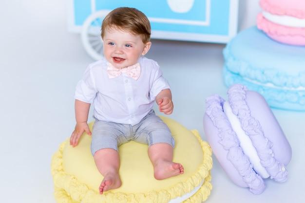 Retrato de menino muito adorável, sentado no biscoito grande e sorrindo. Foto Premium