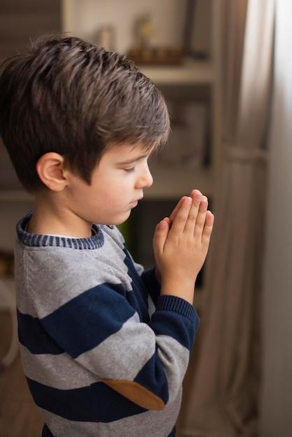 Retrato de menino rezando Foto gratuita