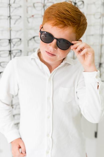 Retrato de menino sardento vestindo óculos pretos na loja de óptica Foto gratuita