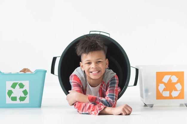 Retrato de menino sorridente posando com caixas de reciclagem Foto gratuita