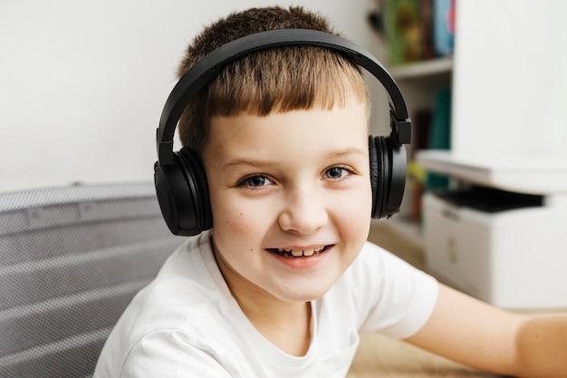 Retrato de menino usando fones de ouvido no computador Foto gratuita