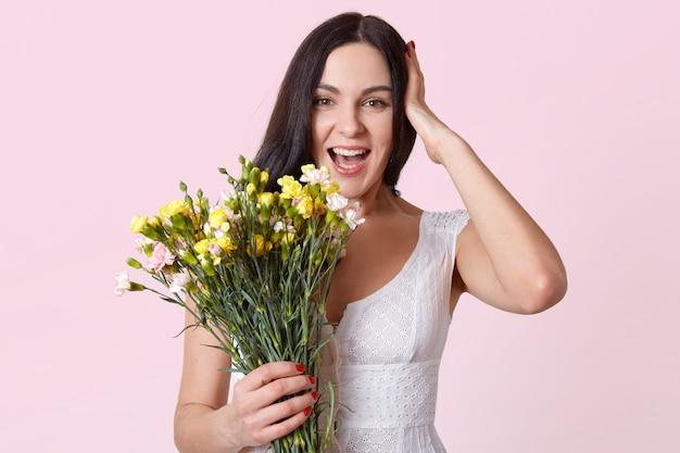 Retrato de metade do comprimento da mulher bonita morena segurando ramo de flores, rindo enquanto olha diretamente para a câmera, mantém a mão na cabeça Foto gratuita
