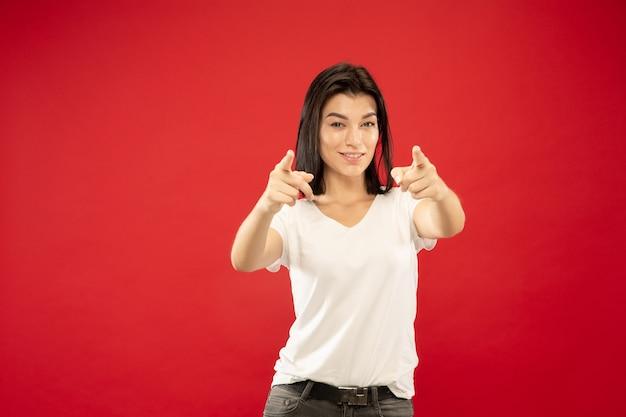 Retrato de metade do corpo de uma jovem caucasiana em estúdio vermelho Foto gratuita