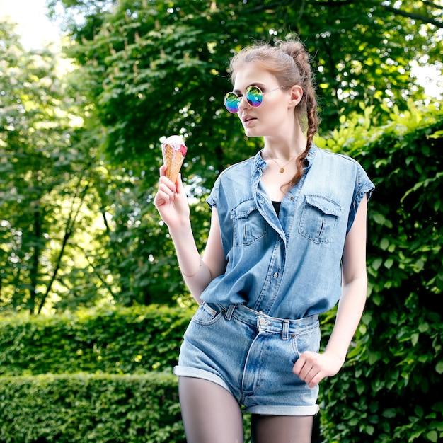 Retrato de moda ao ar livre closeup de garota louca jovem hippie tomando sorvete no tempo quente do verão Foto Premium