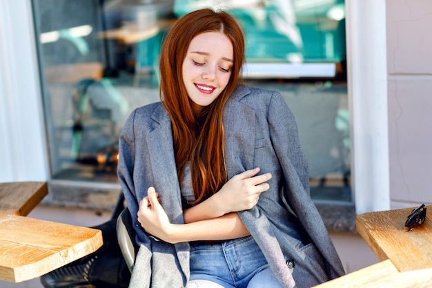 Retrato de moda ao ar livre da elegante mulher ruiva, posando no terraço do café, em um dia de sol, vestindo jaqueta de namorado, cores brilhantes e frescas. Foto gratuita