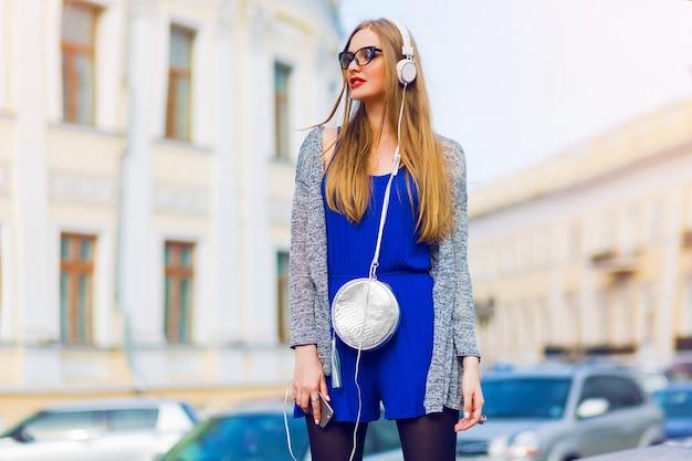 Retrato de moda ao ar livre de elegante mulher casual com fones de ouvido em macacão azul, bolsa prata posando contra ruas. apreciando uma música adorável. cores ensolaradas de verão. Foto gratuita