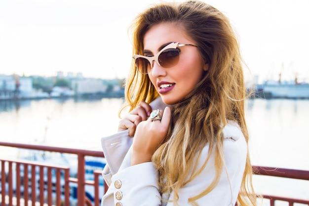Retrato de moda ao ar livre de sedutora sensual linda mulher posando no porto marítimo, à luz do sol de noite, usando óculos escuros de ouro de luxo elegante e casaco de cashmere. Foto gratuita