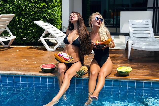 Retrato de moda ao ar livre para duas amigas lindas se divertindo perto da festa na piscina, segurando doces frutas tropicais, biquíni sexy, óculos de sol, diversão na empresa, tomando banho de sol. Foto gratuita