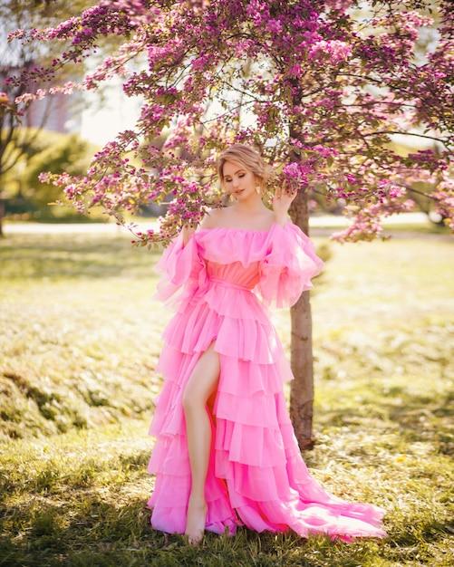 Retrato de moda arte de uma bela jovem loira em um jardim de primavera rosa florescendo em um vestido longo rosa como uma princesa em conto de fadas Foto Premium
