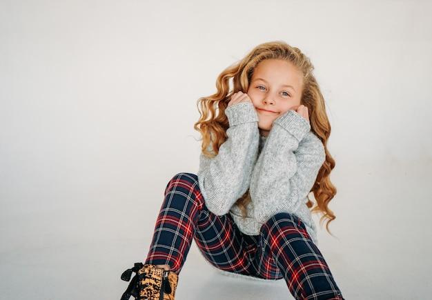Retrato de moda beleza de sorrir garota de cabelo encaracolado tween na camisola de malha aconchegante e calças xadrez em branco isolado Foto Premium