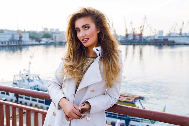 Retrato de moda outono ao ar livre de senhora elegante sexy posando bonito porto marítimo, sonhando e pensando, vestindo um casaco branco de caxemira branco tem cabelos cacheados e maquiagem brilhante. sol da tarde, cores suaves. Foto gratuita
