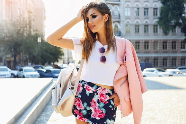 Retrato de moda rua ao ar livre moda de mulher bonita com roupa casual de outono andando na cidade. linda menina morena ou estudante desfrutando fins de semana. Foto gratuita