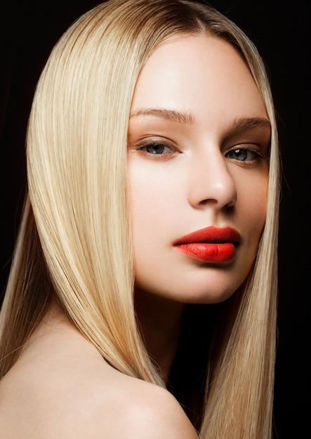 Retrato de modelo de moda beleza com penteado loiro brilhante com lábios vermelhos em fundo preto Foto Premium