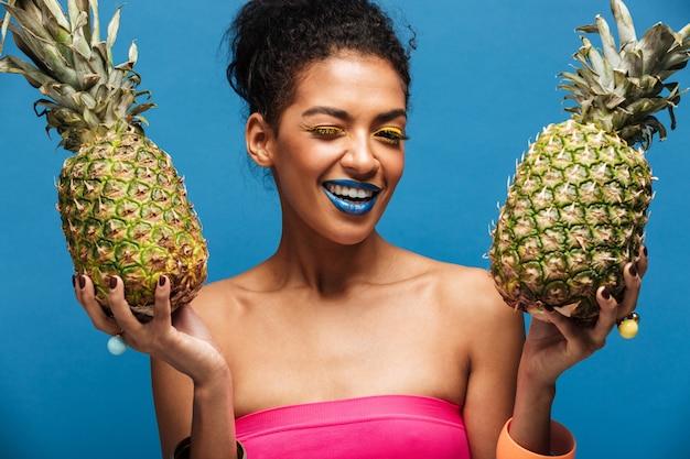Retrato de mulata alegre com maquiagem elegante piscando enquanto segura dois abacaxis suculentos em ambas as mãos isoladas, sobre a parede azul Foto gratuita