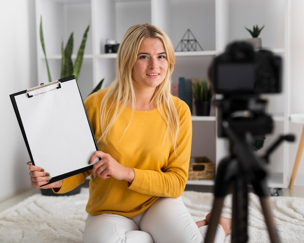 Retrato de mulher adulta gravando vídeo em casa Foto gratuita