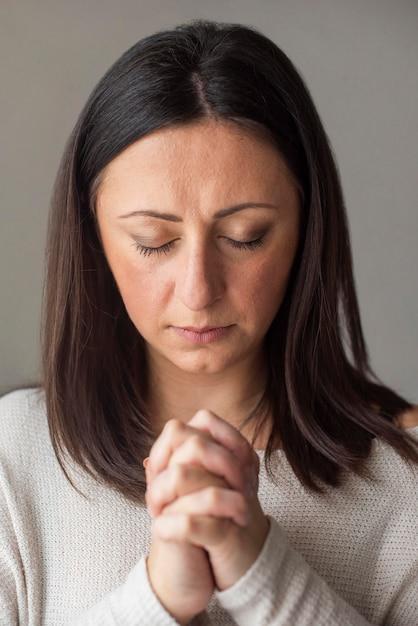 Retrato de mulher adulta, rezando em casa Foto gratuita