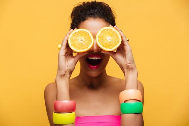Retrato de mulher afro-americana divertida com acessórios de moda se divertindo e cobrindo os olhos com duas metades da laranja isolado, sobre parede amarela Foto gratuita