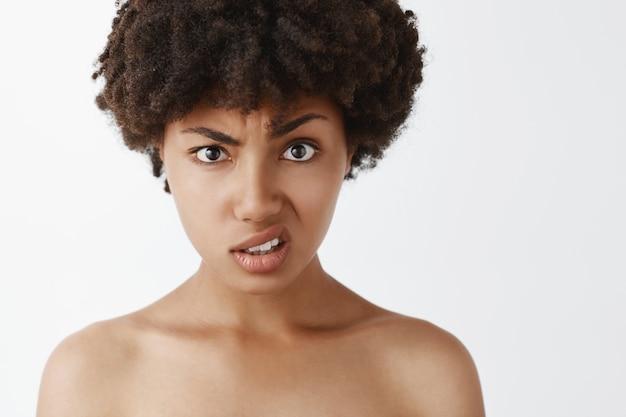 Retrato de mulher afro-americana intensa questionada e sem noção com penteado afro, levantando sobrancelha e lábio superior, sendo confundida com pessoa estúpida Foto gratuita
