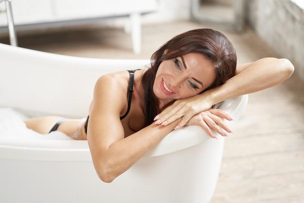 Retrato de mulher agradável, tendo prazer no banho Foto Premium