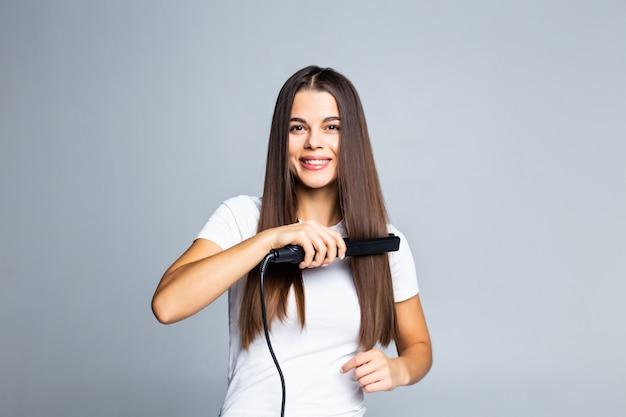 Retrato de mulher alegre usando o alisador de cabelo encaracolado, preparando-se para o evento data feriado confortável penteado fácil isolado em cinza Foto gratuita